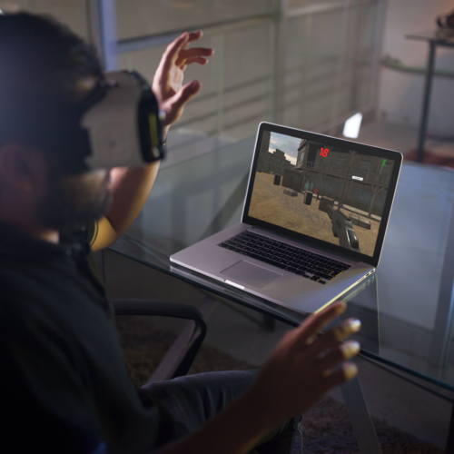 mockup-of-a-young-man-wearing-an-oculus-gear-vr-device-while-his-macbook-pro-is-on-the-desk-a14246